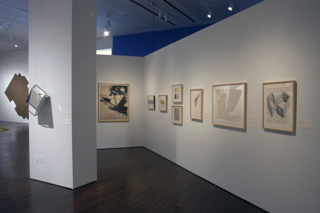 View inside the Reimagining Space exhibition, several artworks on paper are hung on the walls