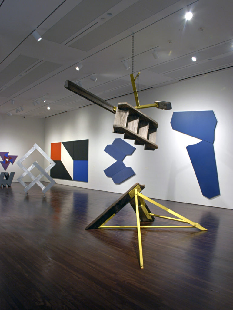 Exhibition View of Reimagining Space: The Park Place Gallery Group in 1960s New York featuring large wood and metal sculptures and colorful paintings