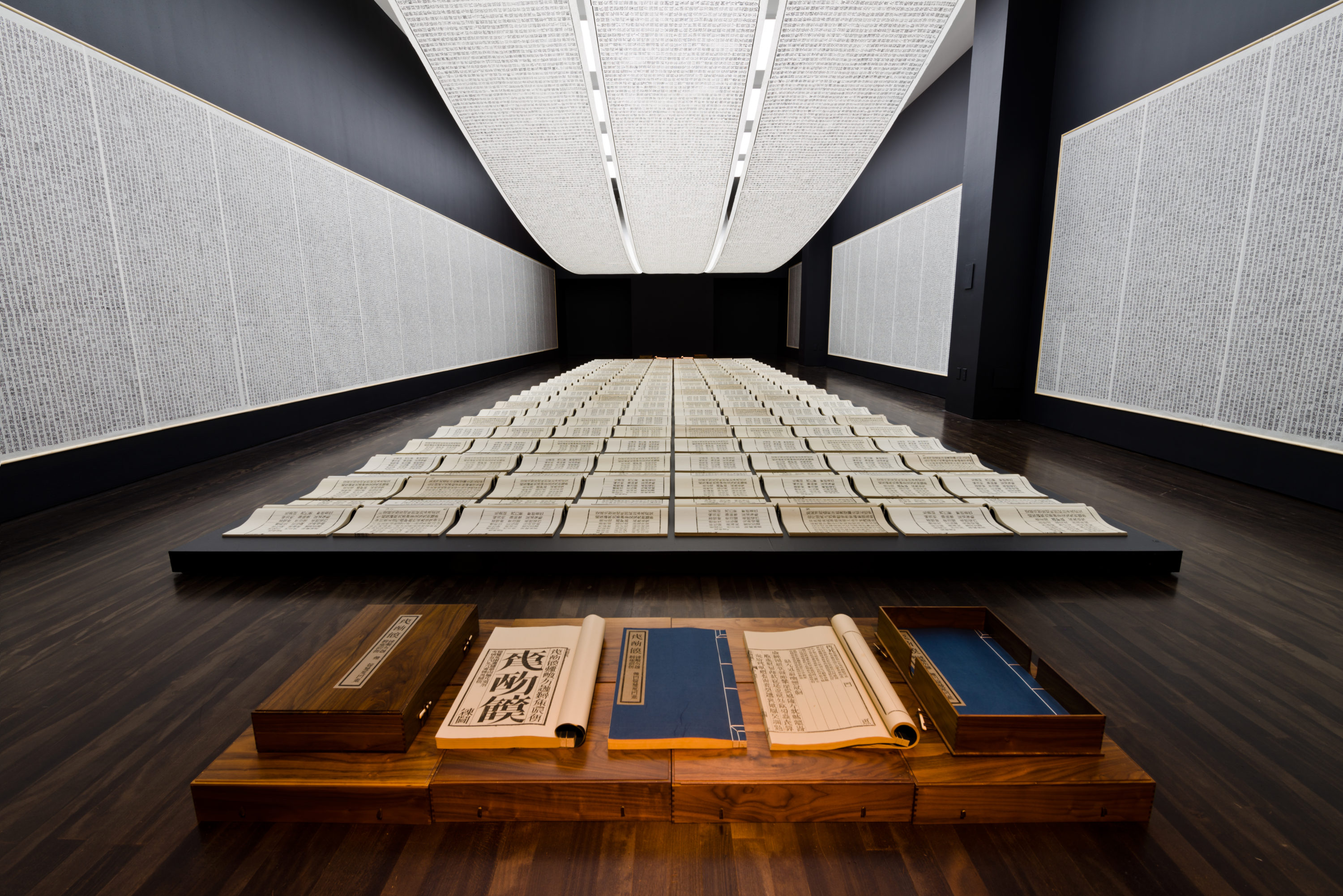 """instlallation view of Xu Bing's """"Book from the Sky from the self titled exhibition. Walls and floor are covered in scrolls and scrolls hanging from the ceiling."""
