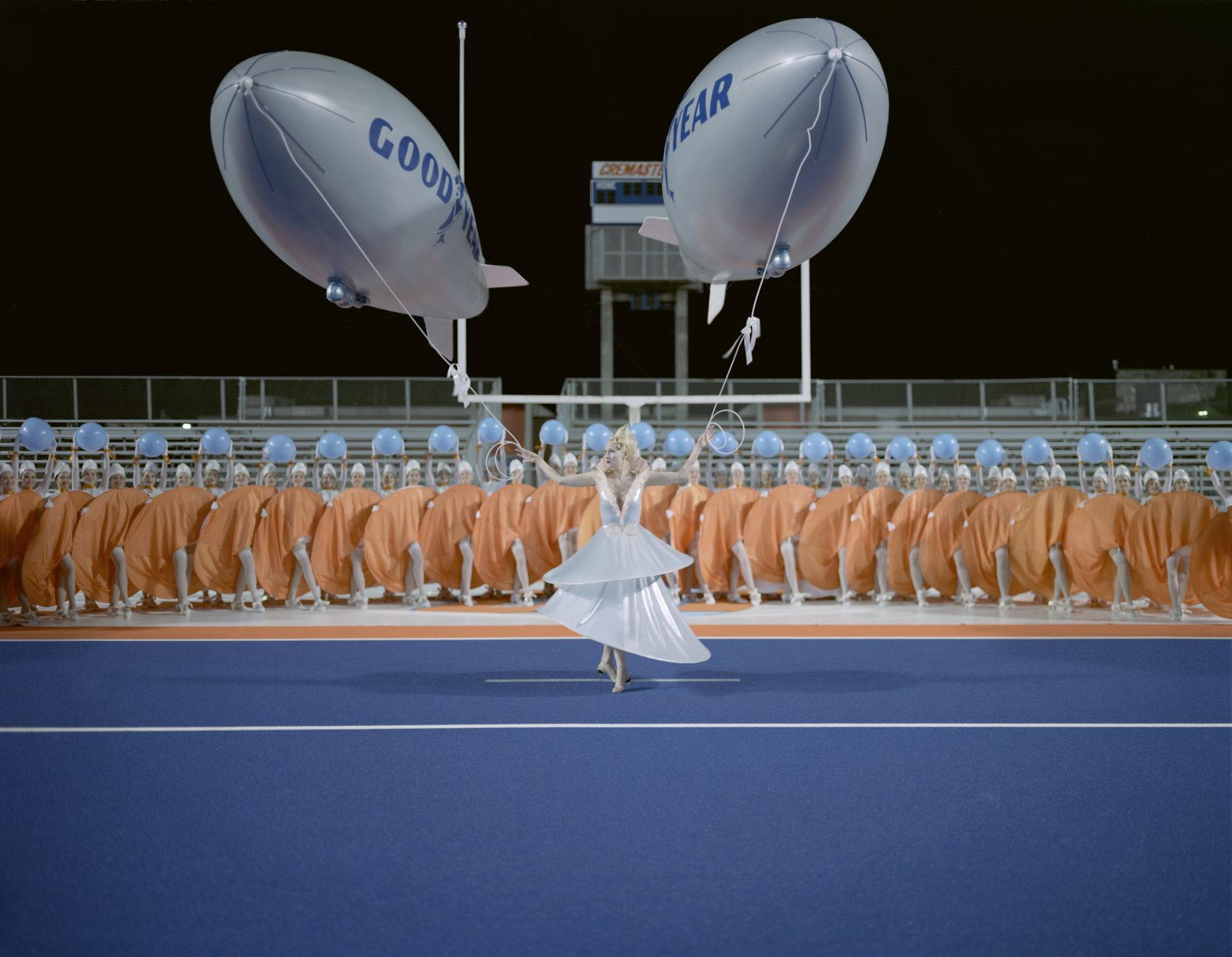 A woman in a retro-futuristic dress stands in a sporting arena, holding two miniature Goodyear blimps by their strings. Behind her, a crowd wearing orange circles watches on
