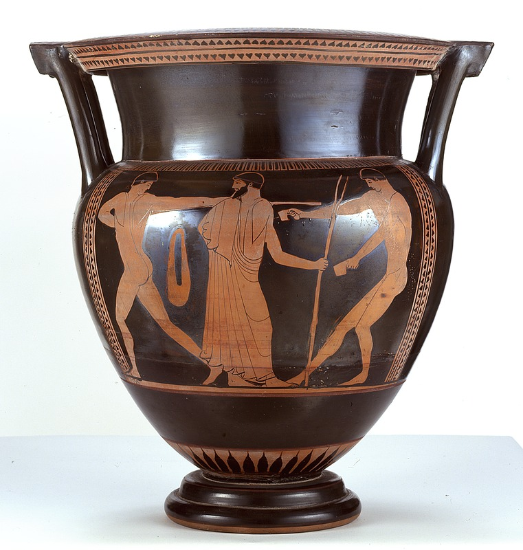 Image depicts a black two-handled vase with three orange figures of men two naked and one in a toga who stands in the middle.