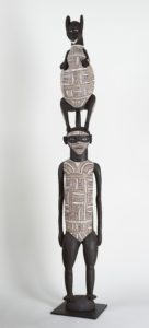 Sculpture of a human type figure with an animal on their head both bodies are covered in an intricate pattern