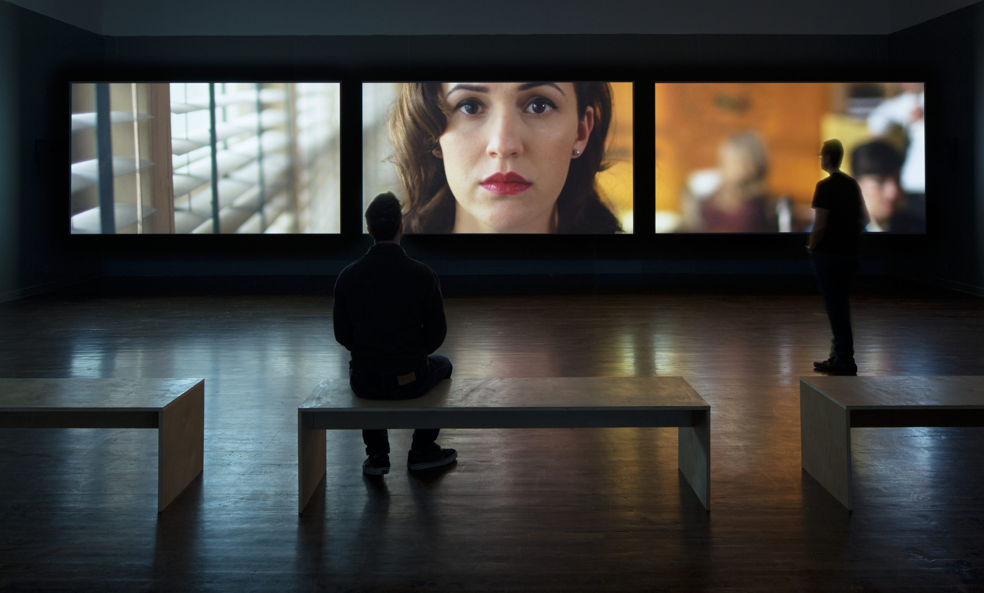 Patron sitting and watching the film artwork Giant, by Theresa Hubbard / Alexander Birchler at the Blanton Museum of Art