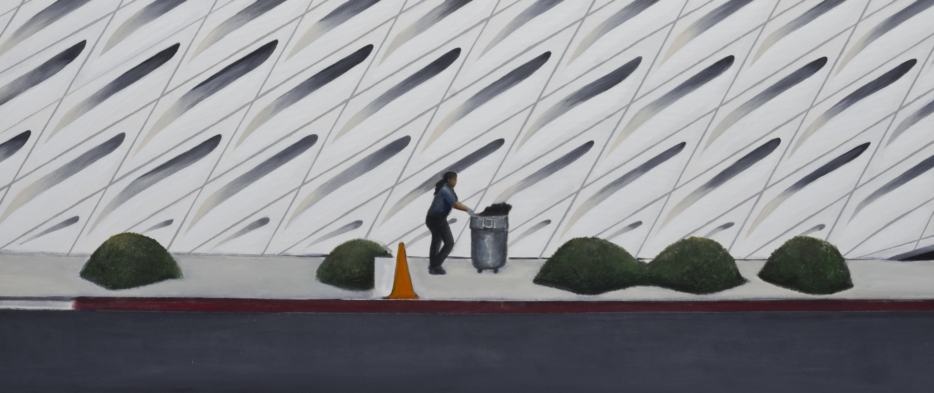 A woman pushes a trash can past the Broad Museum
