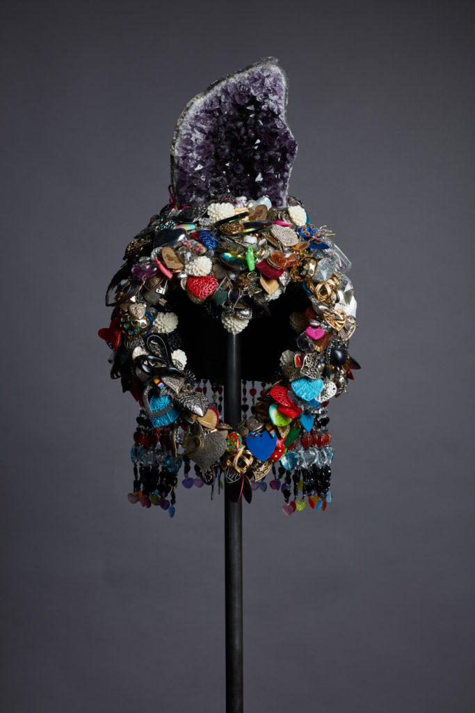 An elaborate helmet made of plastic tchotchkes and a giant geode