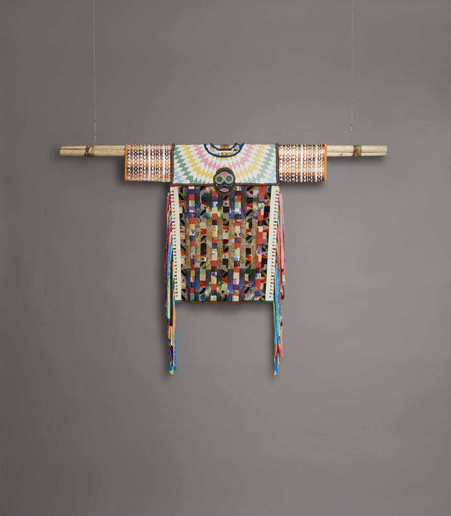 """An elaborate patchwork costume, with """"People Like Us"""" printed on it, is hung from the ceiling"""