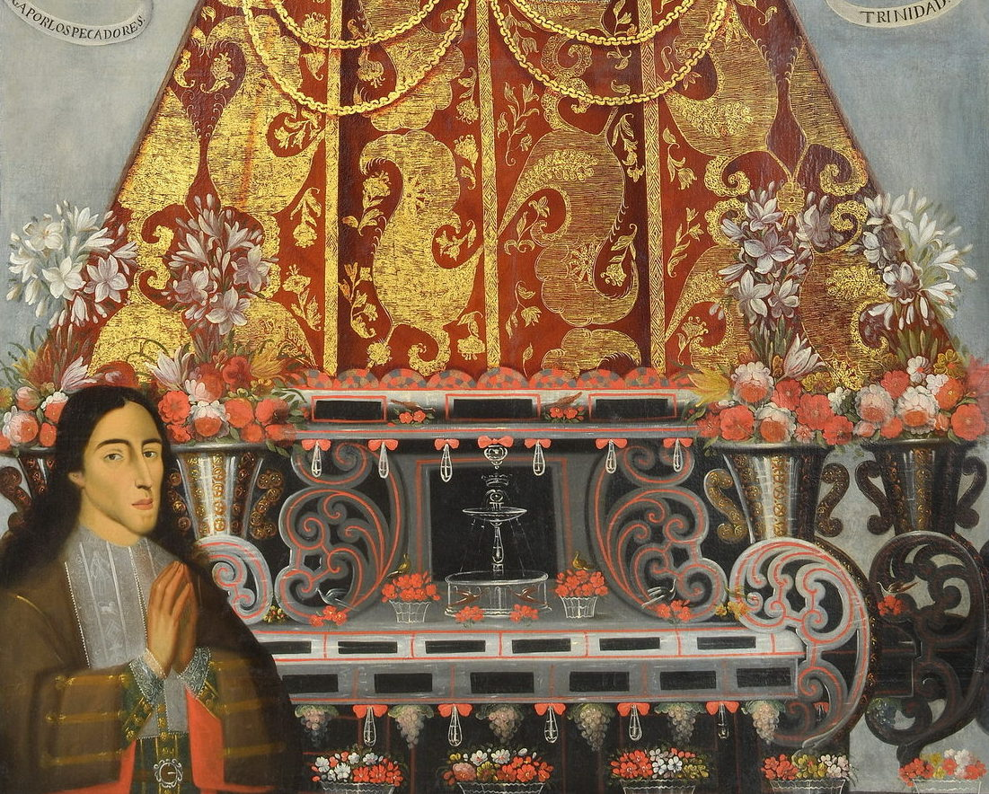 close up of the donor with his hands in prayer at the bottom of the lady of bethlehem statue. the bottom of the statue is ornate and surrounded with baskets and vases full of fresh flowers
