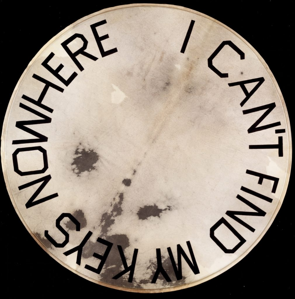 """Artwork by Ed Ruscha, a drumskin head with """"I Can't Find My Keys Nowhere"""" painted on it"""