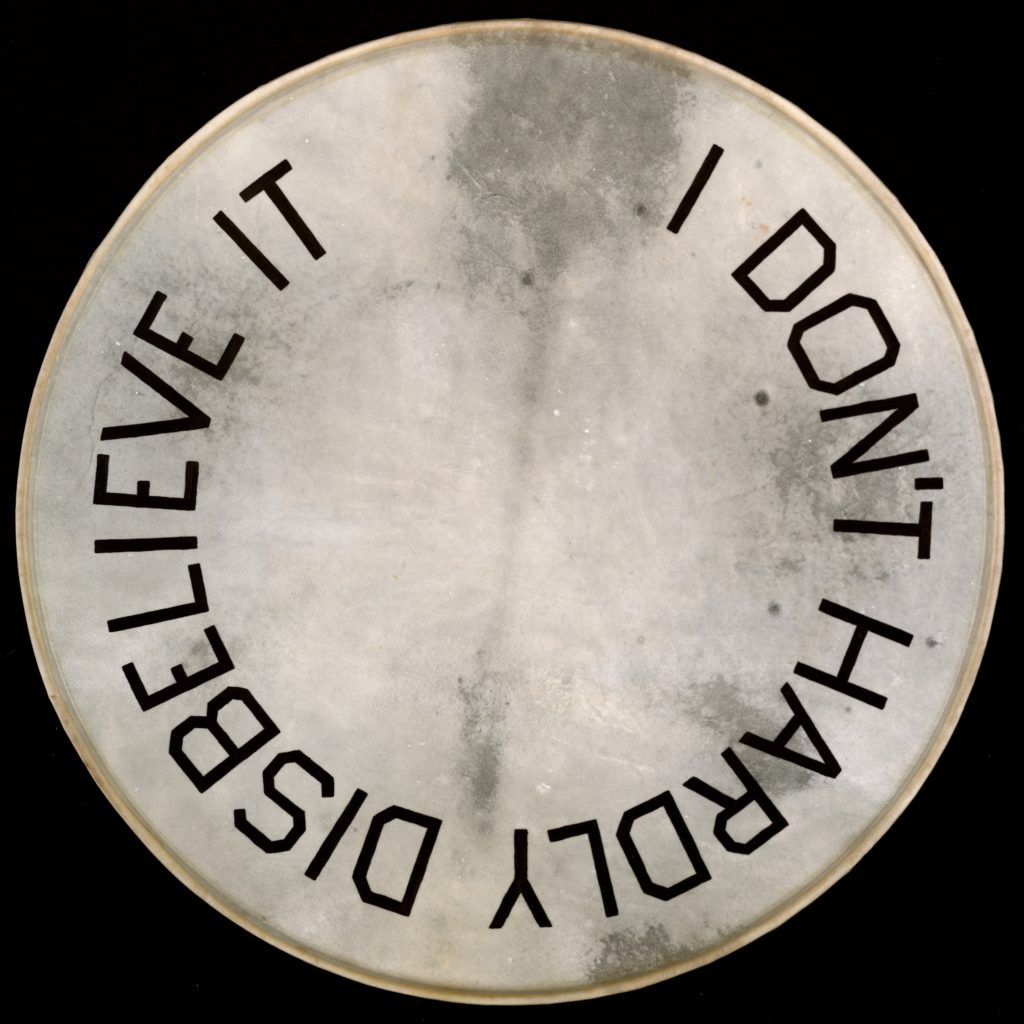 """Artwork by Ed Ruscha, a drumskin head with """"I Don't Hardly Disbelieve It"""" painted on it"""
