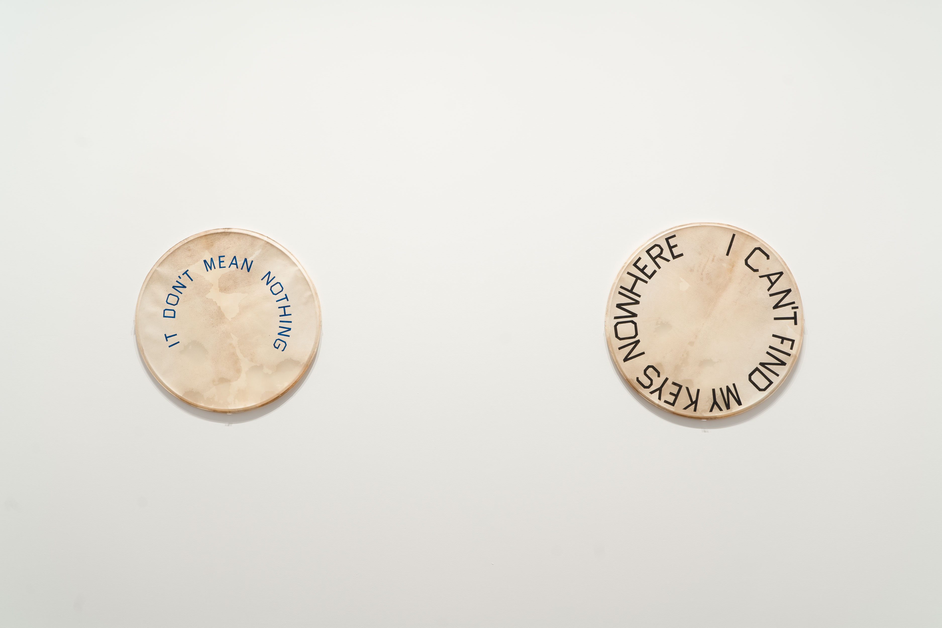 Photo of two drum skins hanging on the wall with writing on, taken during the installation of Ed Ruscha: Drum Skins exhibition at the Blanton Museum of Art.