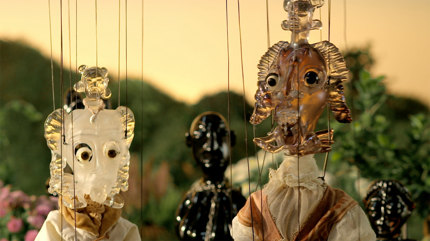 Image still from video of glass puppets on strings.