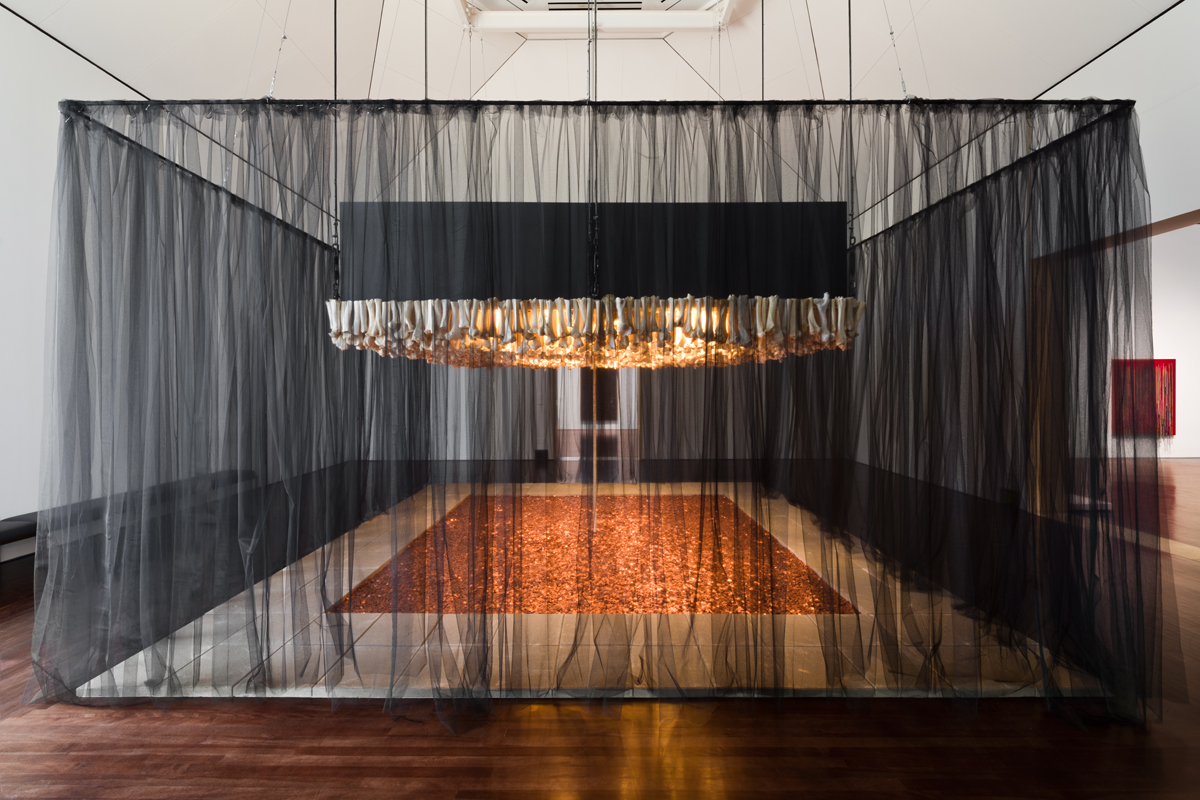 "Photo of Cildo Meireles' Missão/Missões [Mission/Missions] (How to Build Cathedrals) , 1987. The piece is made up of 600,000 coins, 800 communion wafers, 2,000 cattle bones, 80 paving stones, and black cloth. The paving stones are positioned into a rectangle with the interior being full of pennies. In the middle of the pit of pennies is a stack of communion wafers that go towards the top of the piece. The top of the piece is a ""roof"" of cattle bones positioned vertically. The entire piece is surrounded by a black cloth."