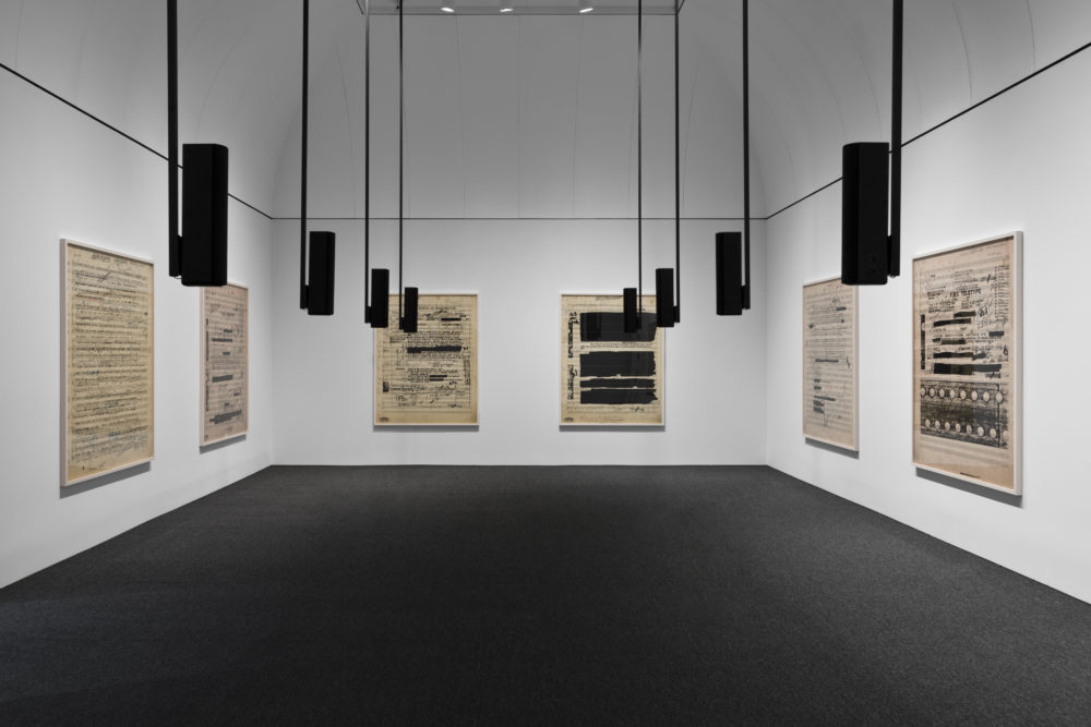 installation view of the contemporary galleries featuring 6 larger than life size framed sheet music with blacked out scales, two per wall, and eight black speakers suspended from the ceiling