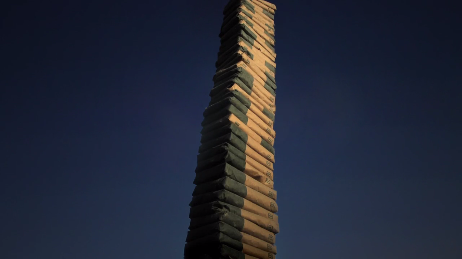 """Film still from """"Coluna Infinita (Infinite Column)"""" by Lais Myrrha, image shows a stack of cement bags marked with half with a dark color and half with a light color reaching vertically out of frame"""