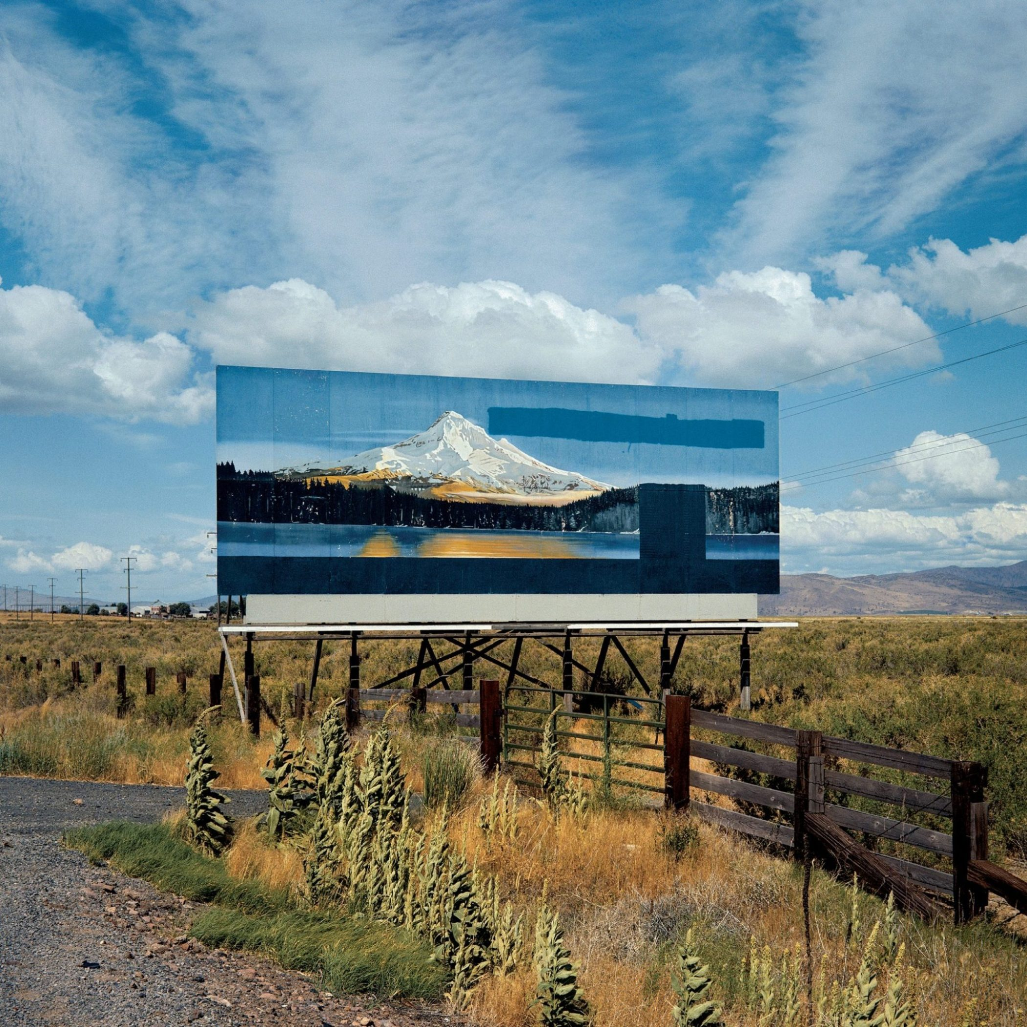 A billboard depicts a snow covered mountain, lake, and pine tree forest. A barbwire and wooden fence separates the billboard from the road. The land is flat and grassy with hills in the background.