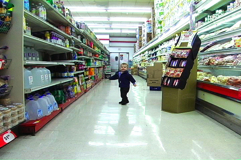 """Still from Lenka Clayton's video series """"The Distance I Can Be From My Son"""" set in a supermarket. Clayton's son stands in the middle of a supermarket aisle looking back at the viewer. The left and right are shelves of groceries. There are boxes and a cardboard grocery display to the right of Clayton's son. Behind him are a set of swinging supermarket doors."""