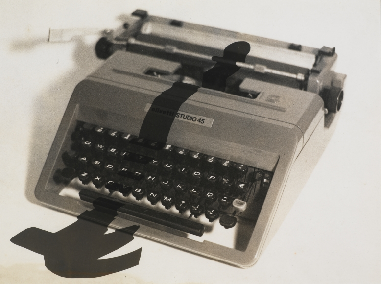 """Photo of """"Enigma 2"""" by Regina Silveira the piece features a typewriter with the shadow of a hammer falling over the keys and in front of the typewriter"""