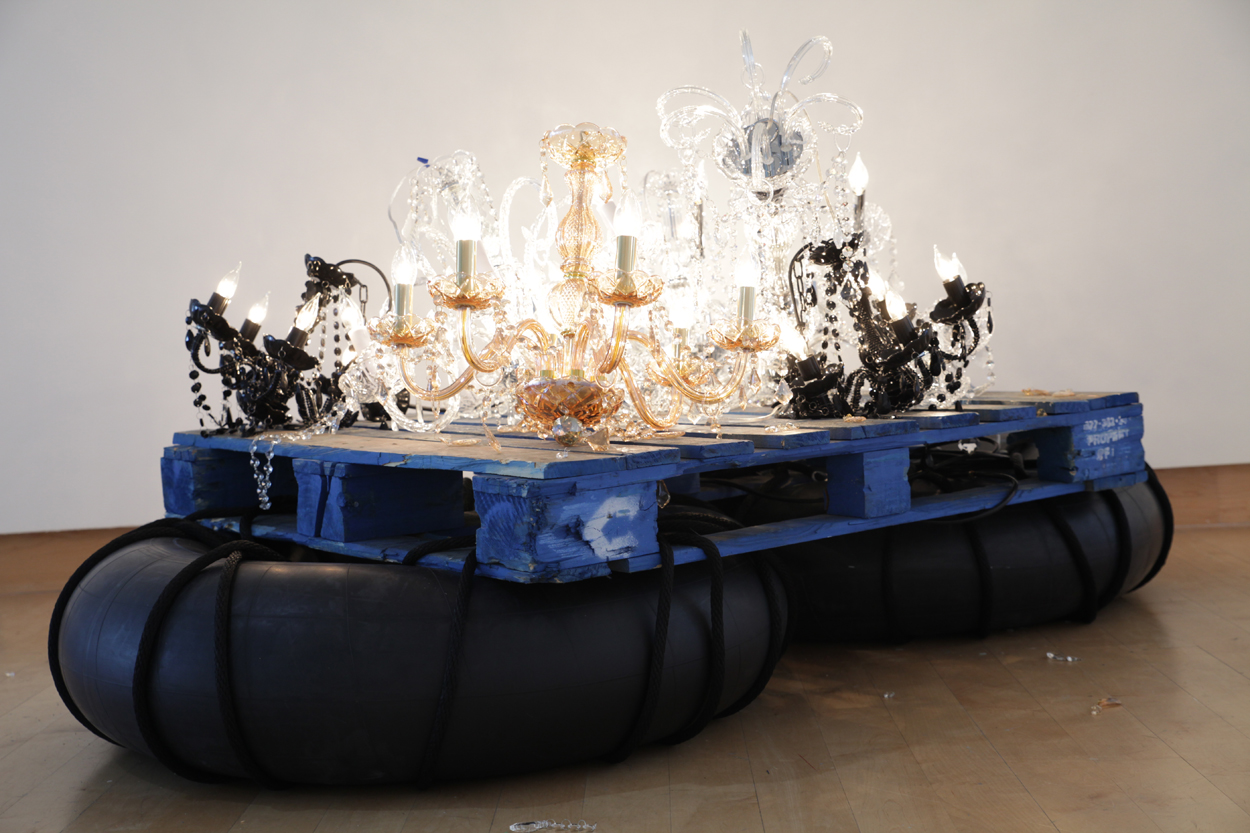Kambui Olujimi's Fathom, 2017. Broken, but still-lit, chandeliers on a raft made of a pallet and rubber tubes