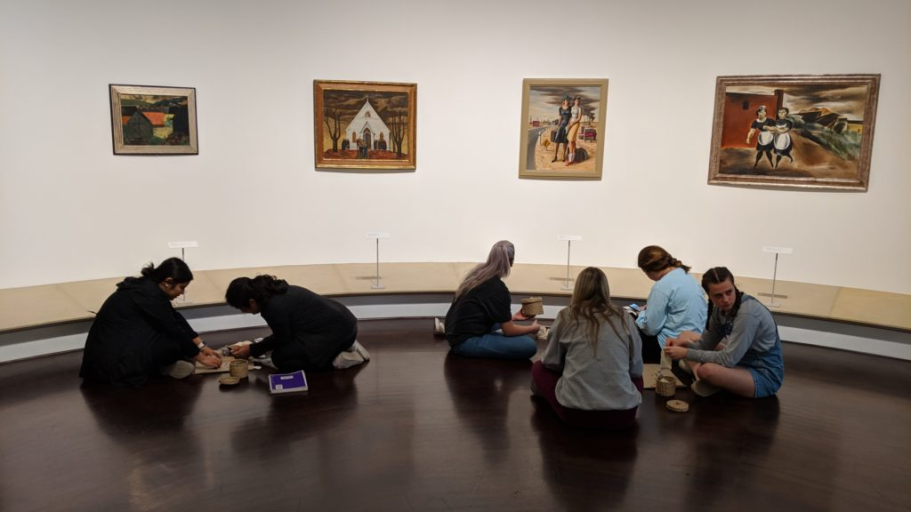 Students working in three small groups, on the ground engaged in activity in front of four pieces of art.