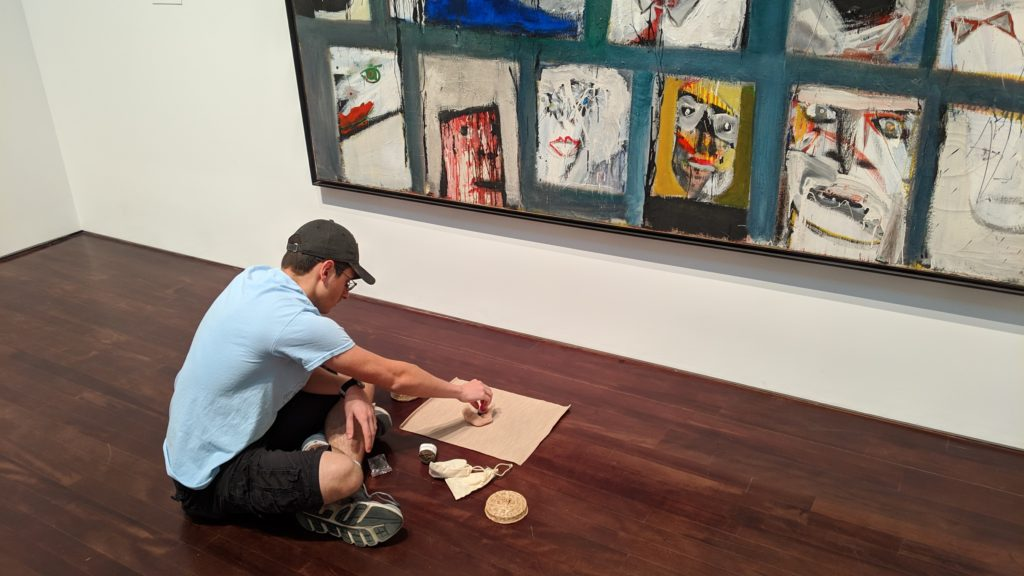 a student is seated on the floor in front of a piece of artwork with a small mat in front of him. He is in the process of creating something