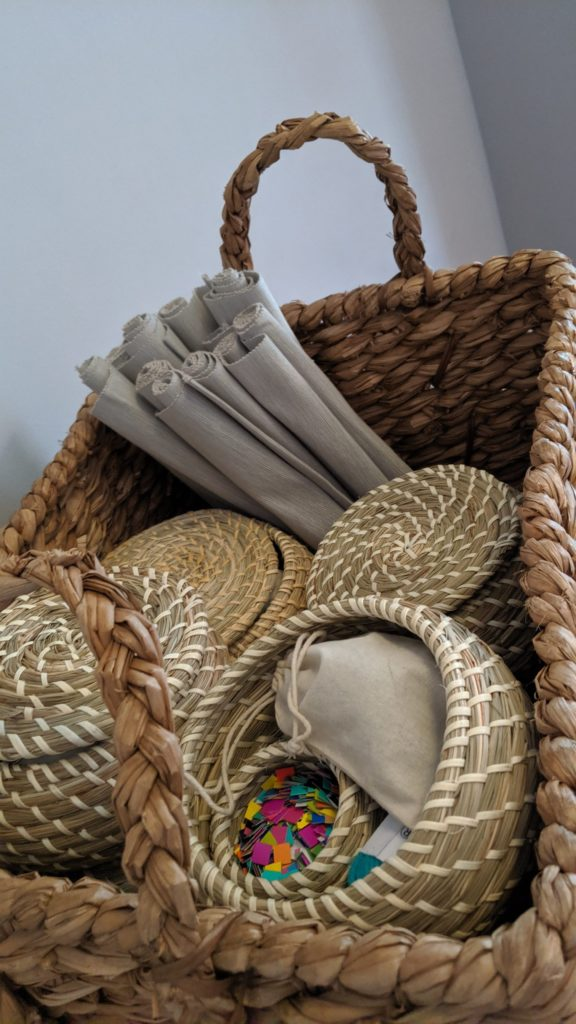 A larger wicker basket that is holding rolled-up mats and holding four mini wicker baskets that contain different supplies like paper and yarn.