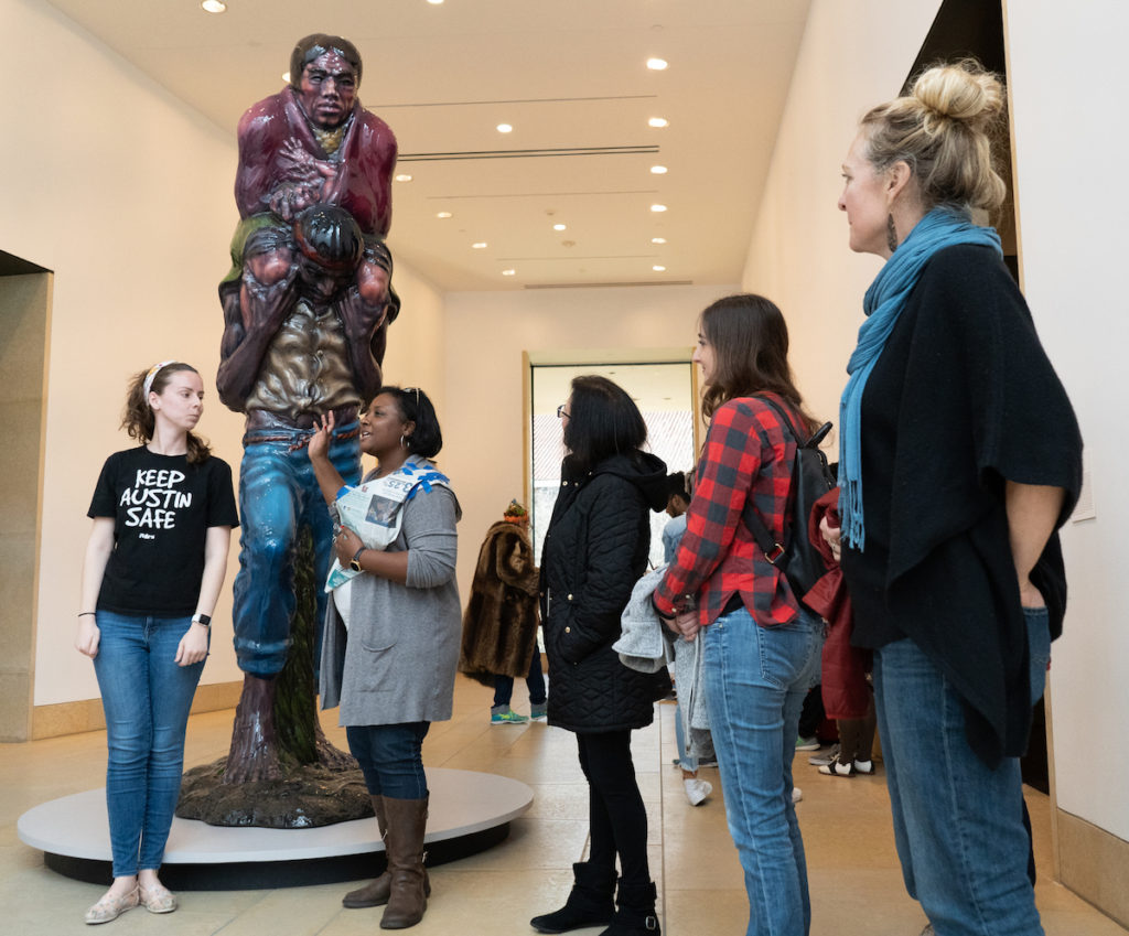 A group of people standing in front of a sculpture at the Blanton, engaging in a corporate team-building exercise.